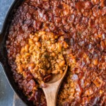 a spoon scooping baked beans out of a skillet