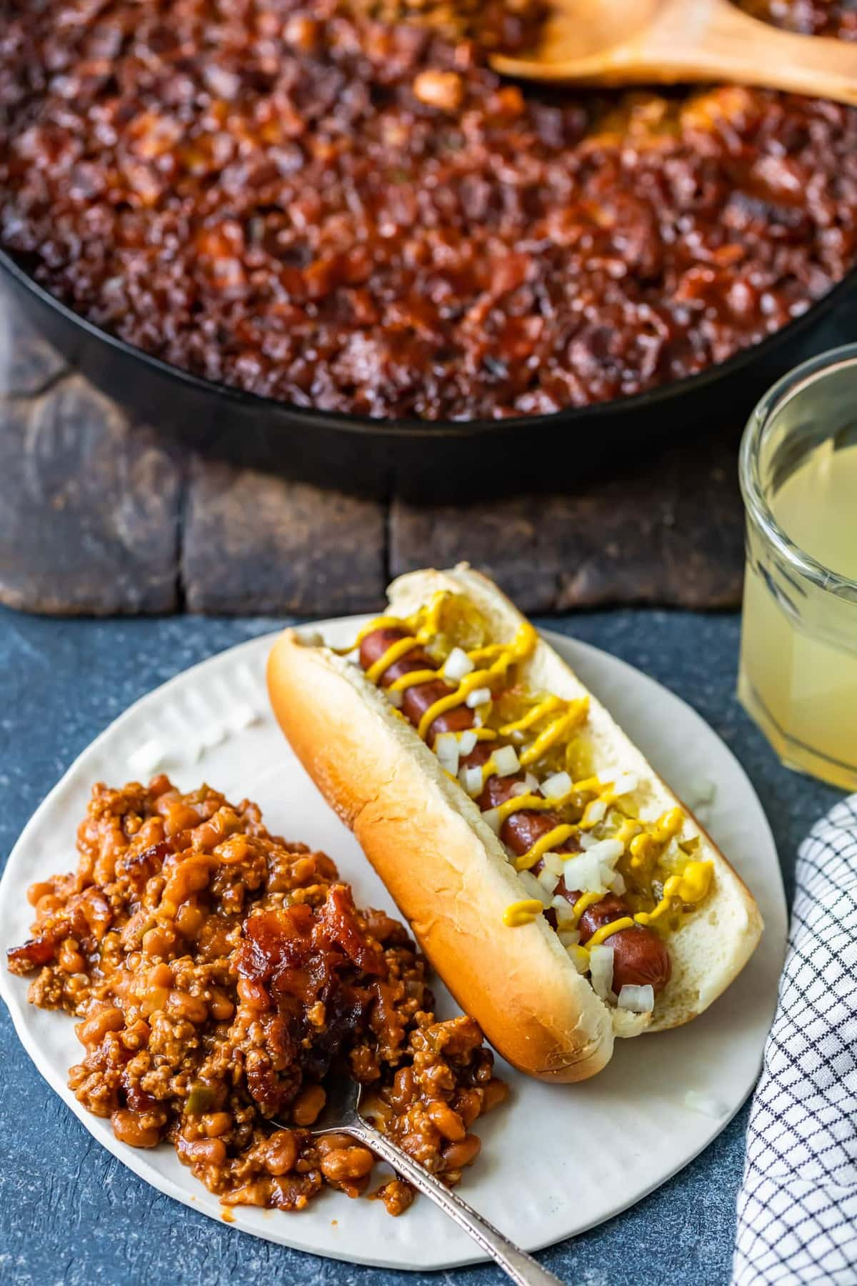 a plate of baked beans and a hot dog