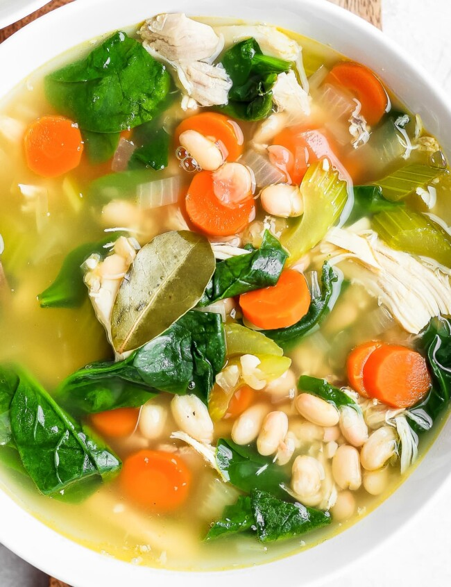 above shot of tuscan chicken soup with carrots and spinach