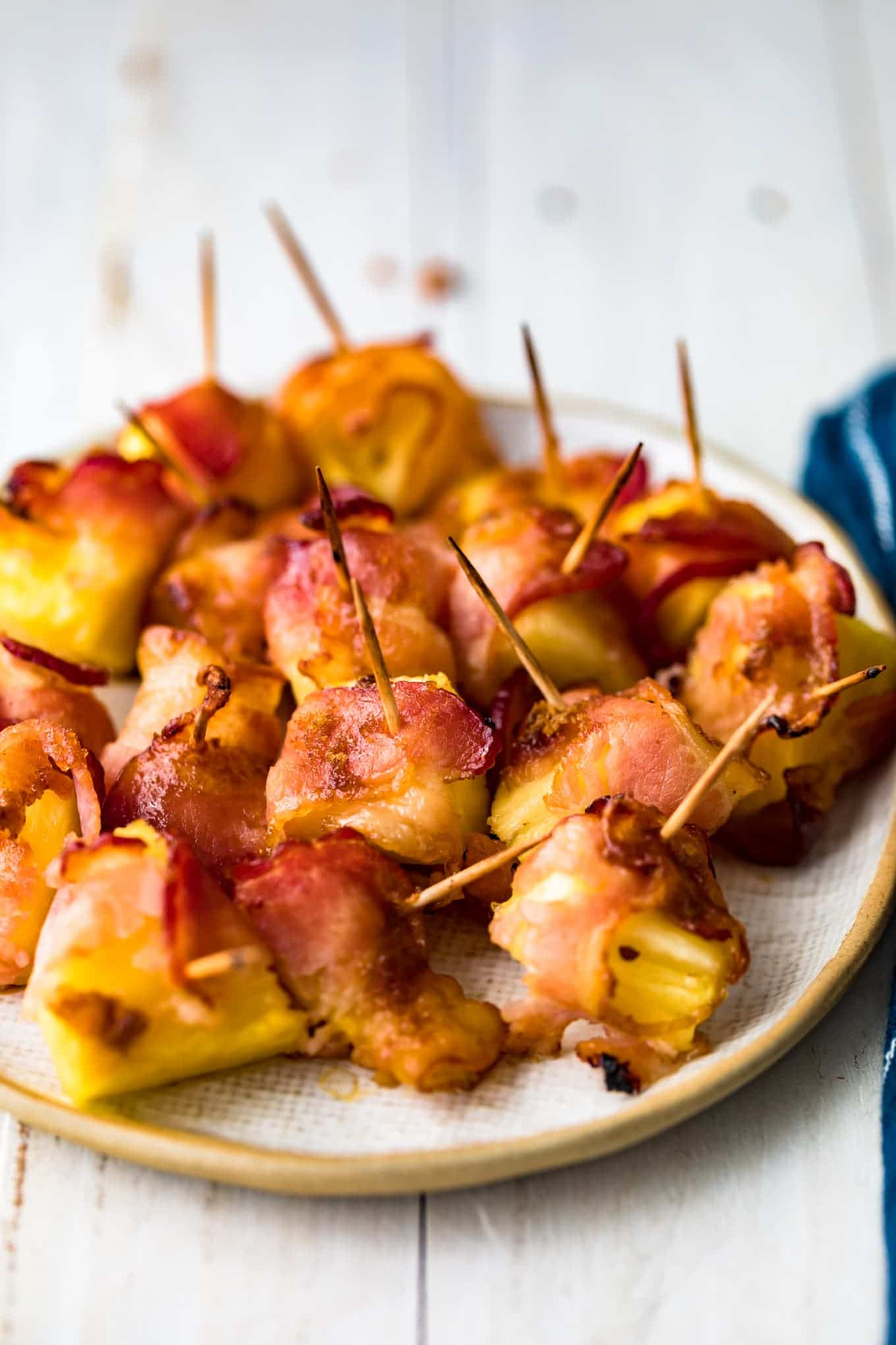Pineapple chunks wrapped in bacon with toothpicks