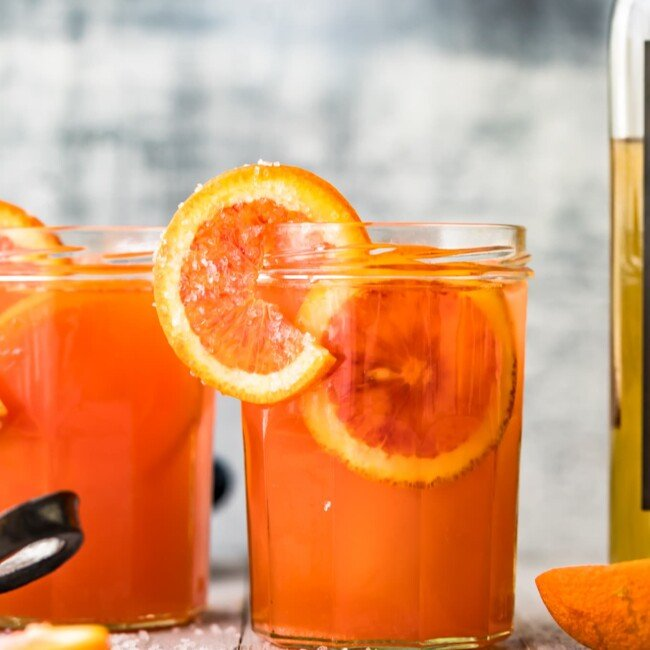 blood orange paloma drink in glass with sliced oranges