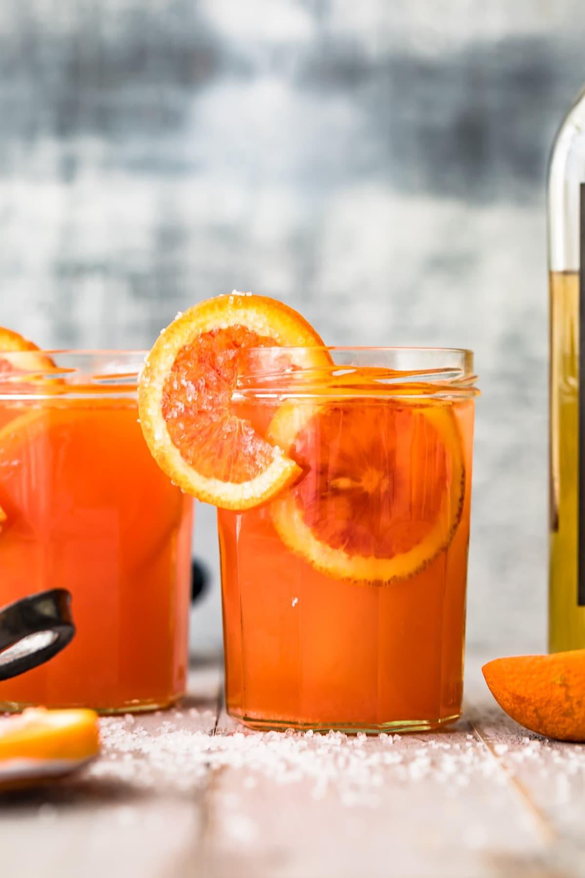 A blood orange cocktail garnished with an orange slice