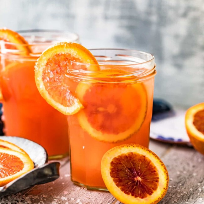 blood orange paloma in glass garnished with oranges