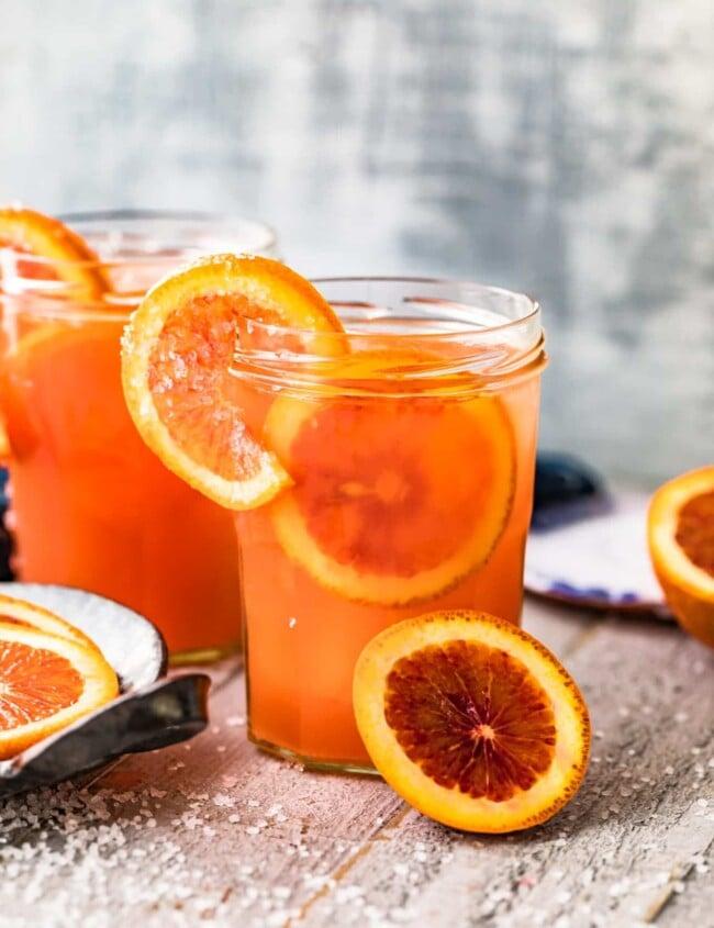 blood orange paloma in glass garnished with oranges