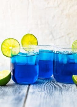 three blue margaritas in glasses topped with sliced limes