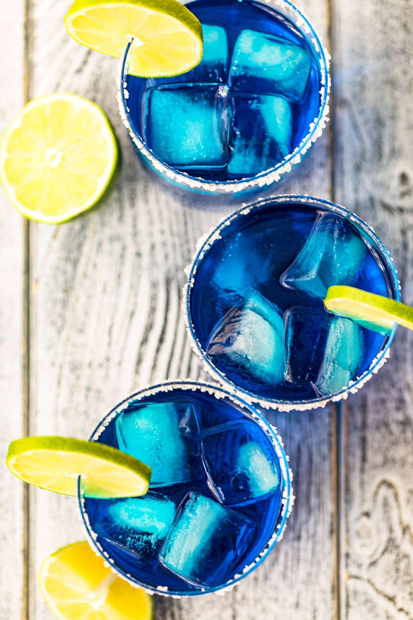 Top down shot of blue margaritas garnished with lime slices