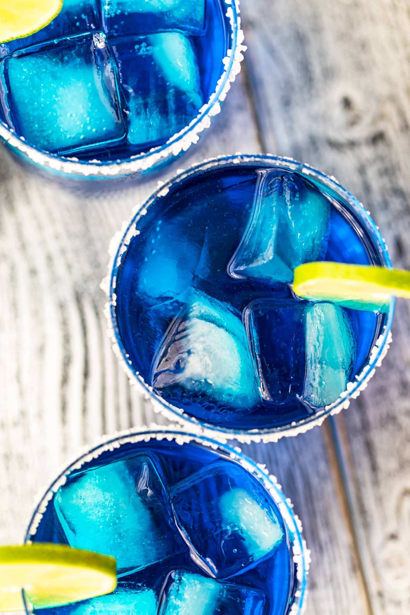 Blue maragaritas in glass with ice and lime slices
