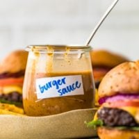 burger sauce in a cup with a spoon and burgers beside it