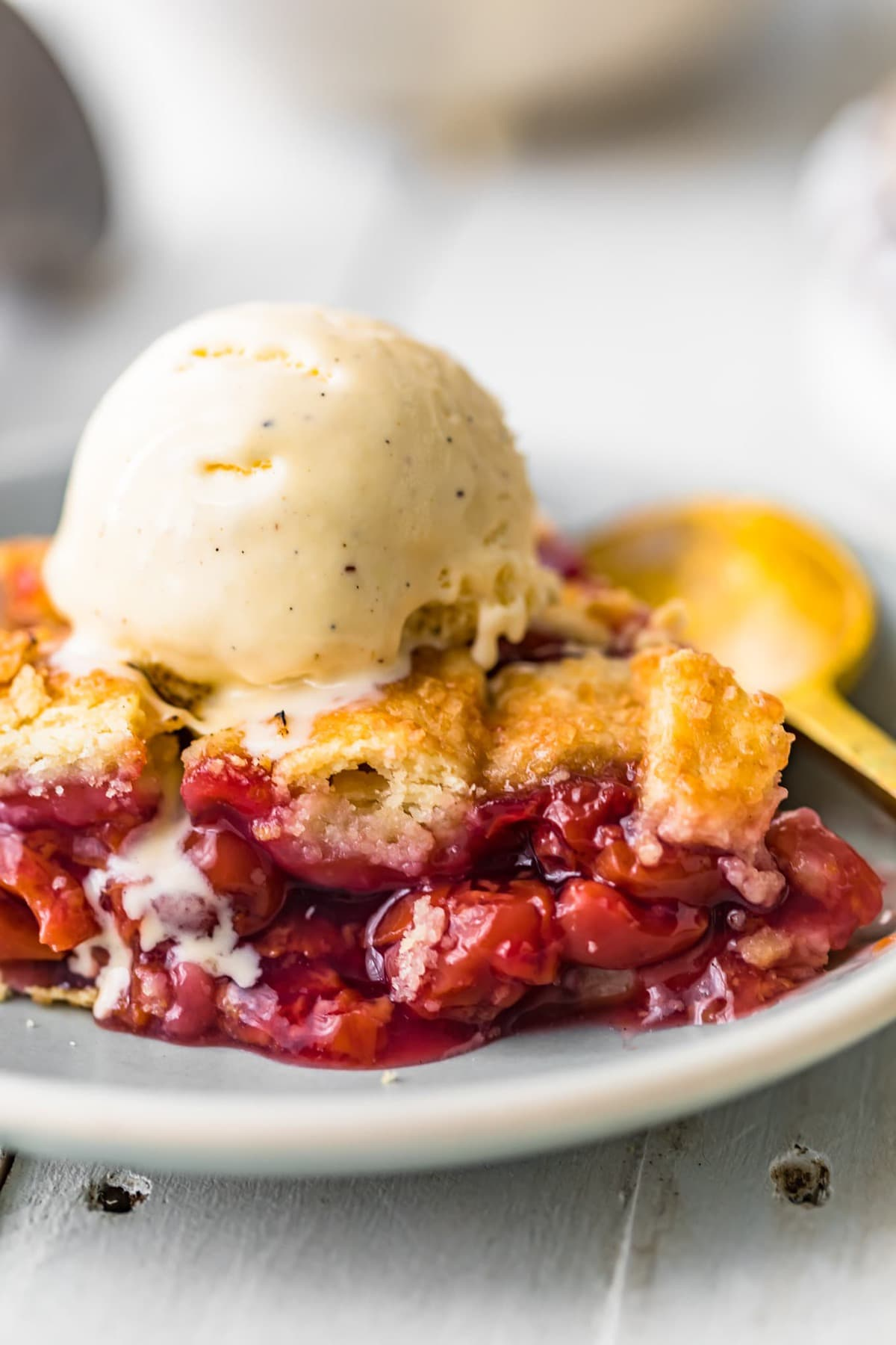 A slice of homemade cherry pie with ice cream on top