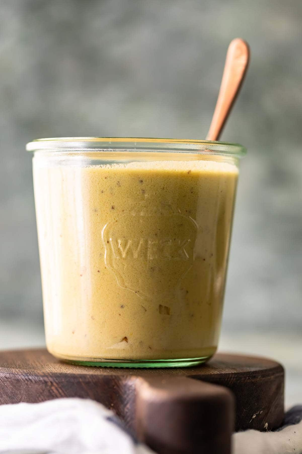 Side view of mustard cream sauce in a glass jar