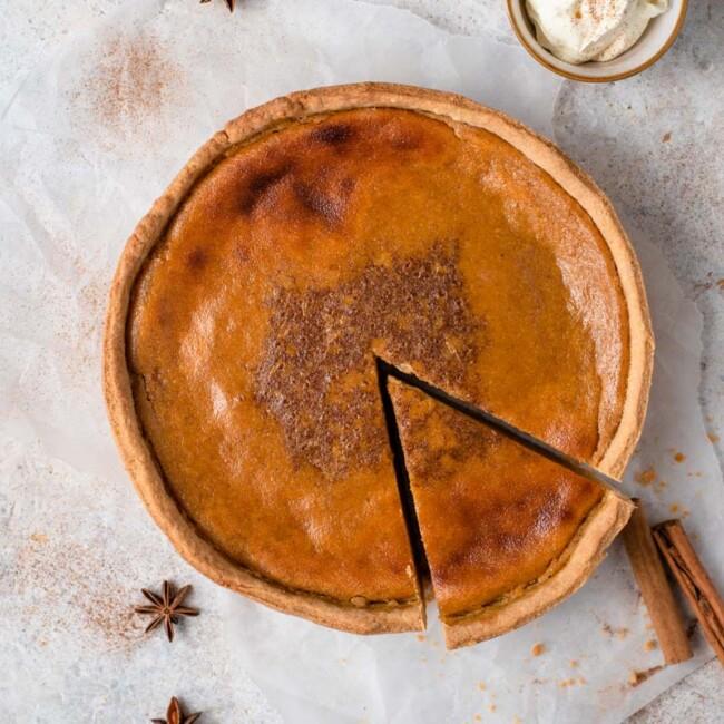 pumpkin pie next to cinnamon sticks