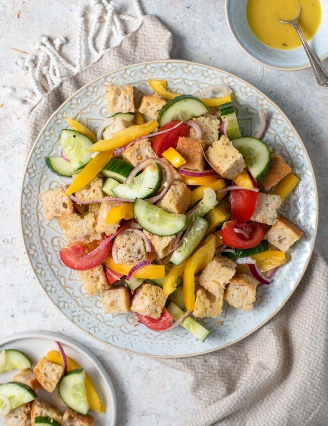 panzanella salad on plate with dressing on the side