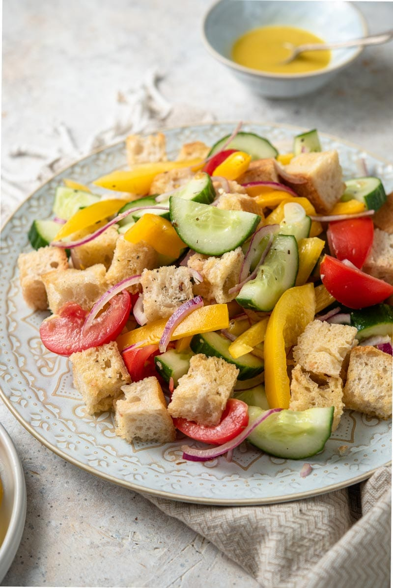 A close up of a panzanella salad on a plate with vinaigrette in the background