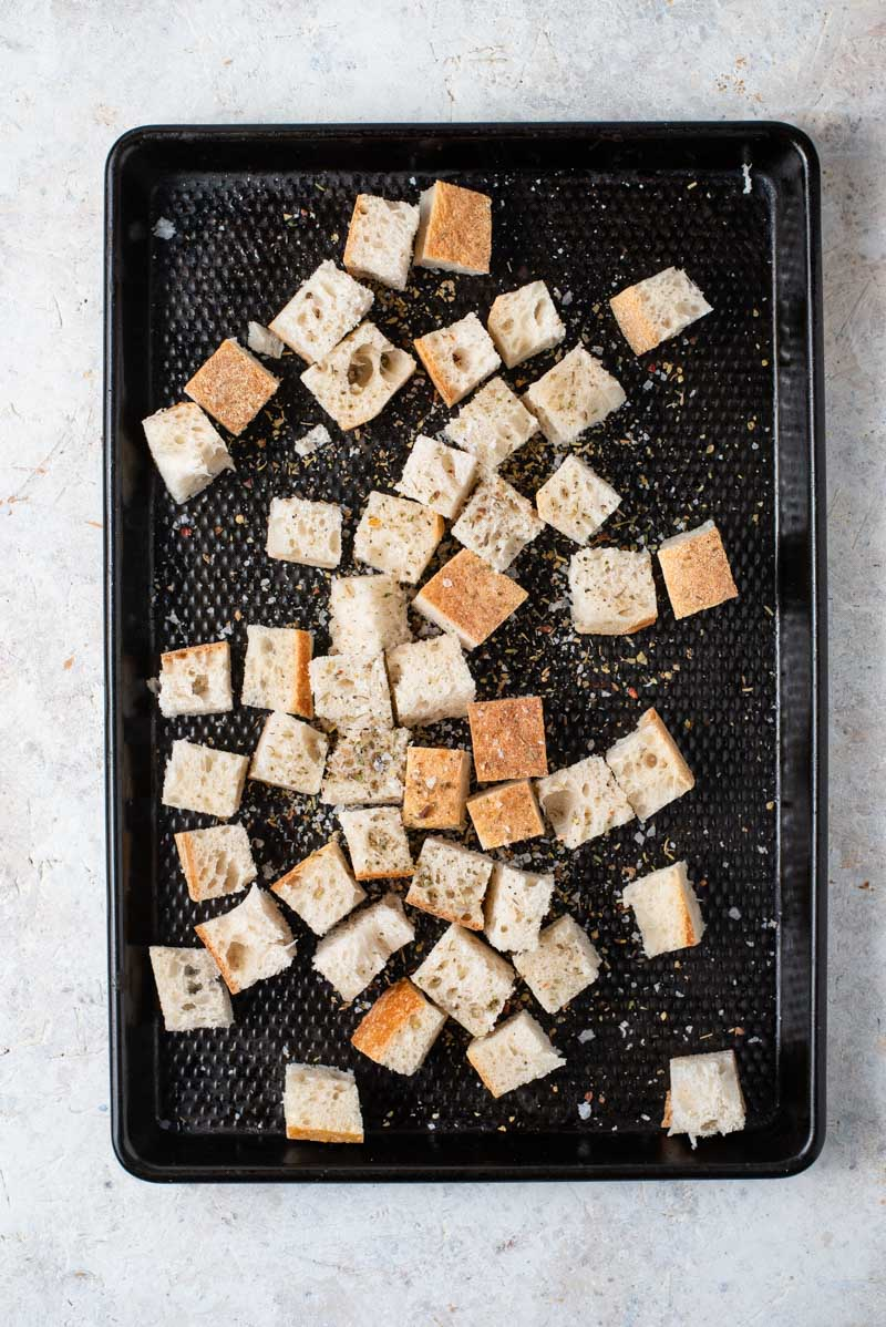 Cubed bread on a baking tray for making panzanella salad