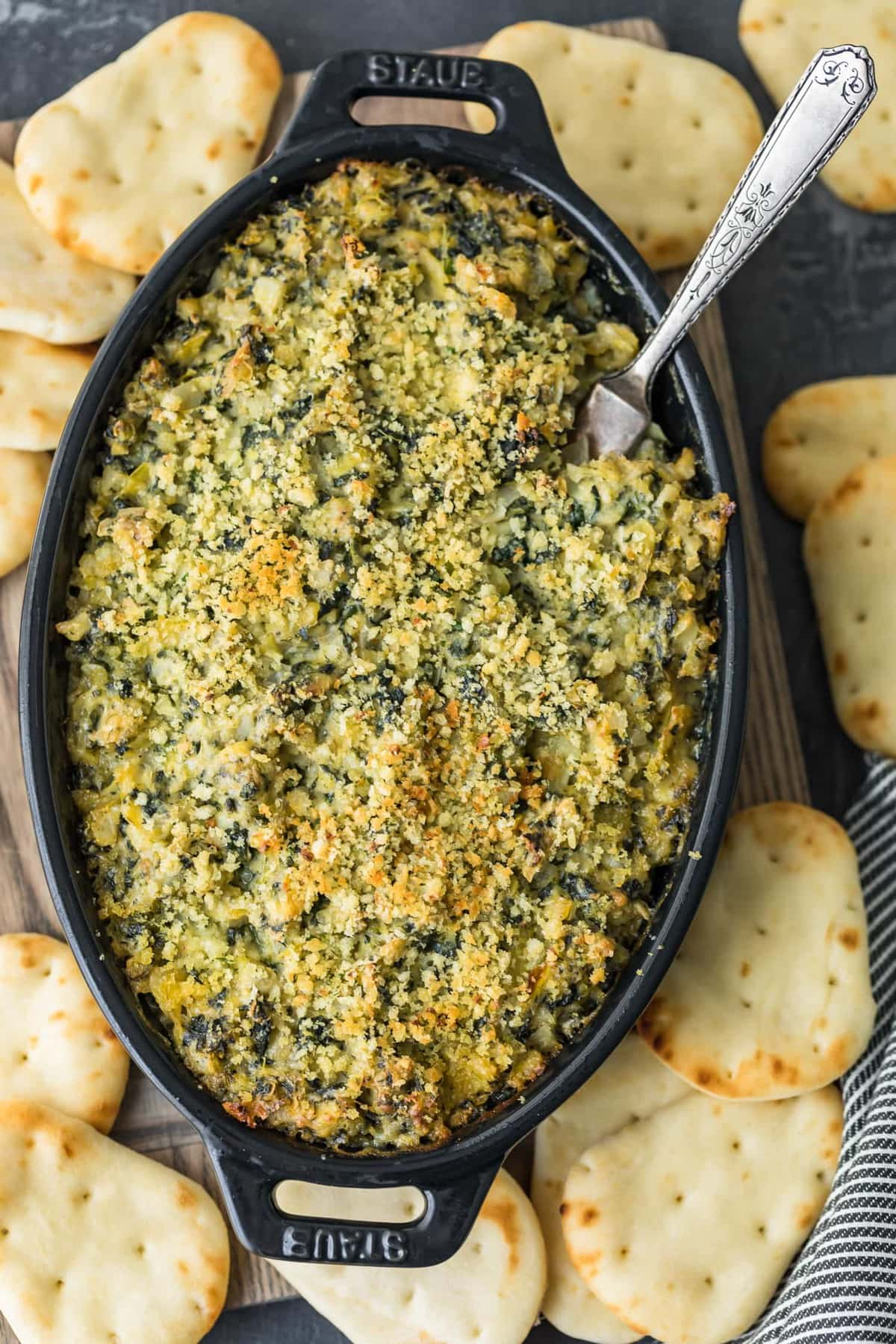 Top shot of Baked Spinach Artichoke Dip in a black dish