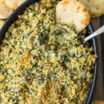 spinach dip in casserole dish with chip