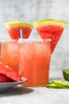 two watermelon margaritas with sliced watermelons on top of the glasses