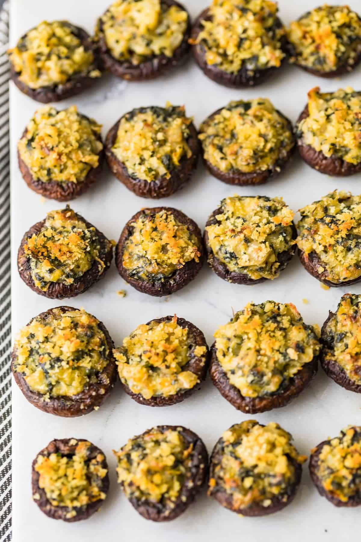 Spinach Stuffed Mushrooms on a white cutting board