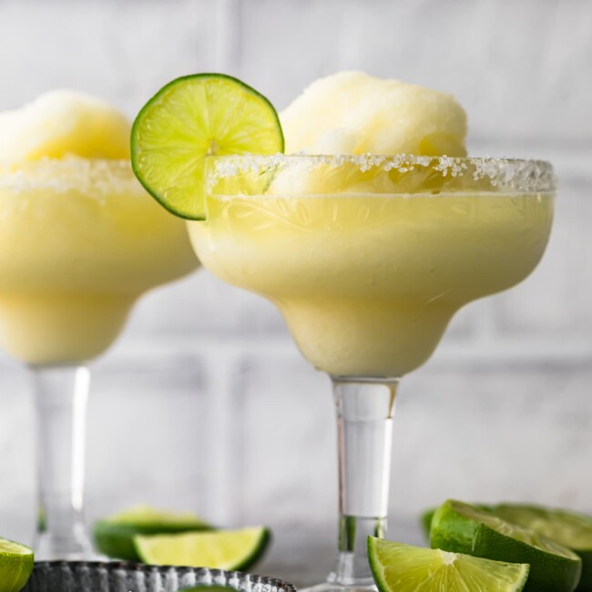 two frozen margarita glasses surrounded by sliced limes