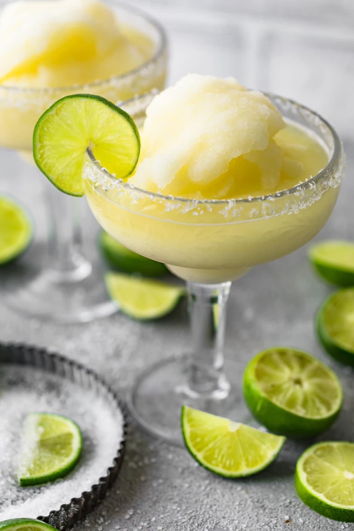A frozen margarita served with a slice of lime