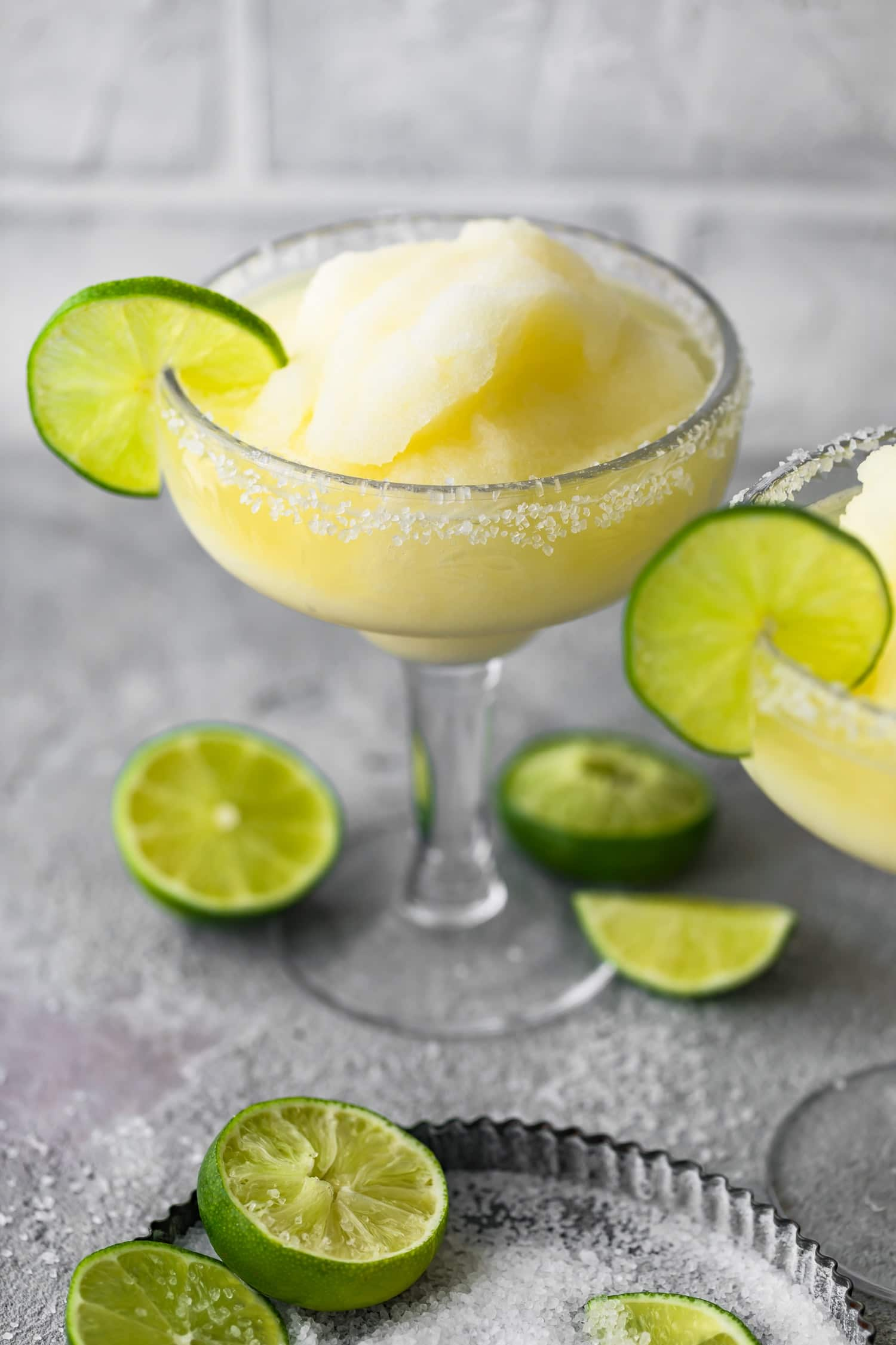 Margarita cocktail in a glass next to lime halves