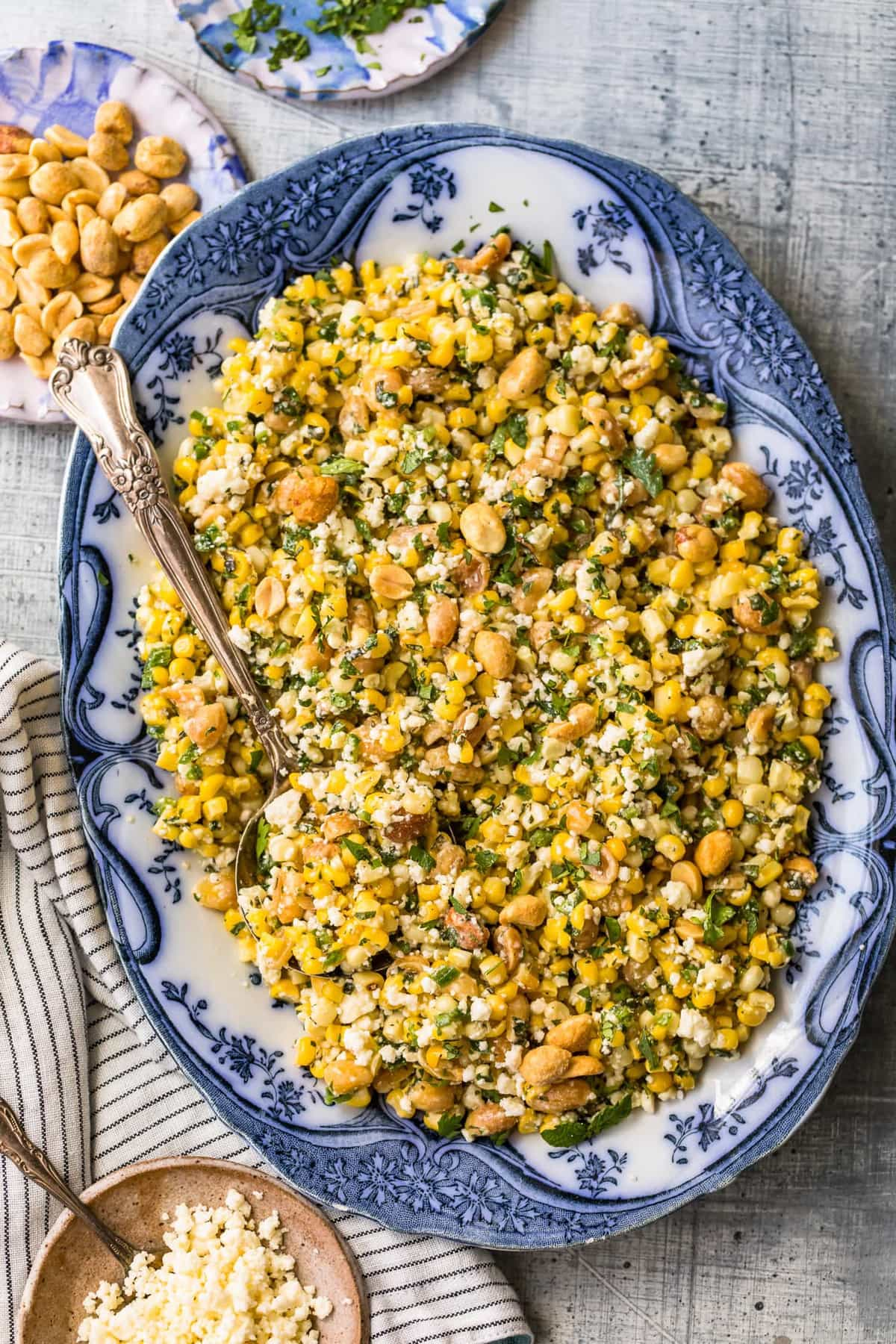 Grilled corn salad on a large serving plate with a spoon