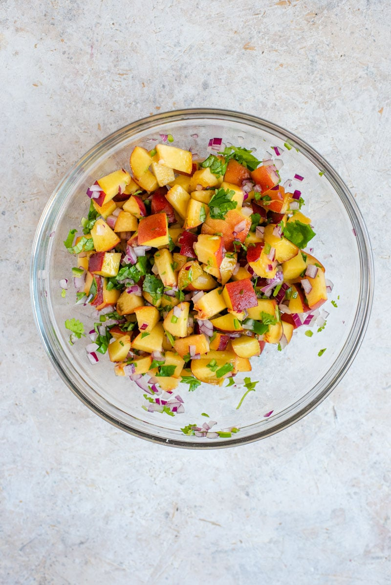 An overhead shot of peach salsa in a bowl for serving with grilled salmon fillet