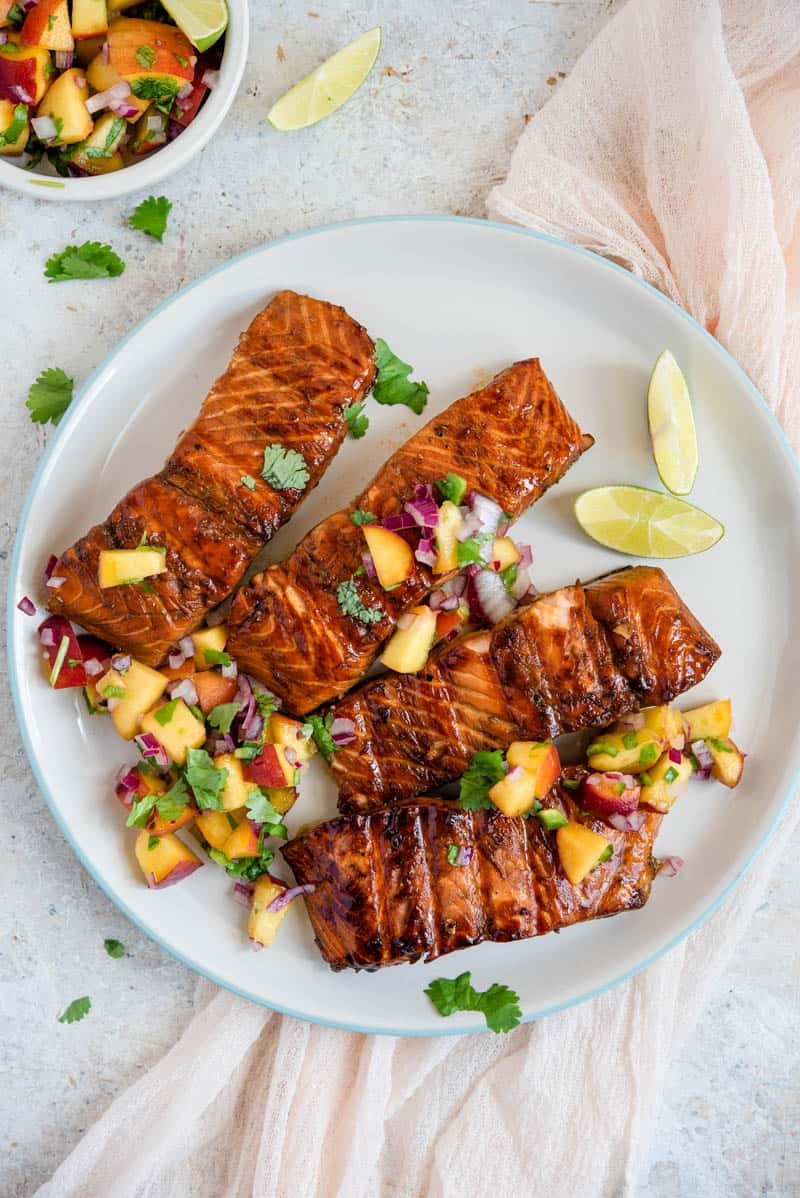 An overhead shot grilled salmon fillets on a plate with peach salsa