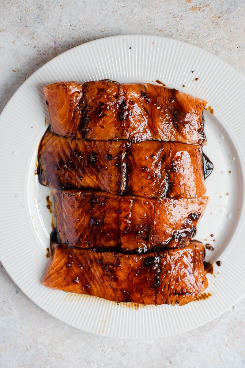 An overhead shot of salmon fillets brushed with a marinade on a plate