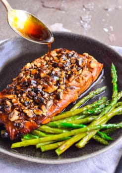 salmon and asparagus in skillet with glaze being spooned on it