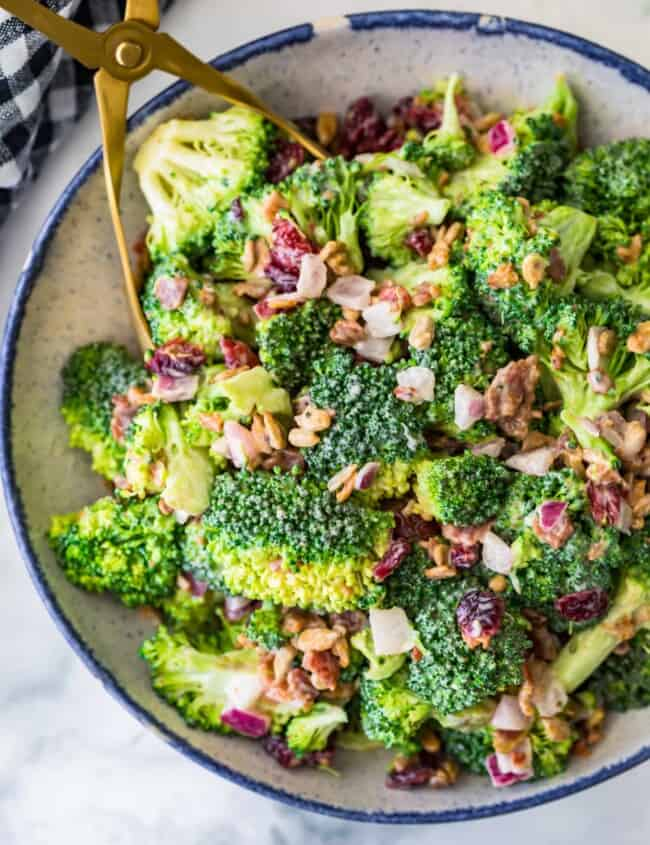 broccoli salad with bacon in a bowl and tongs