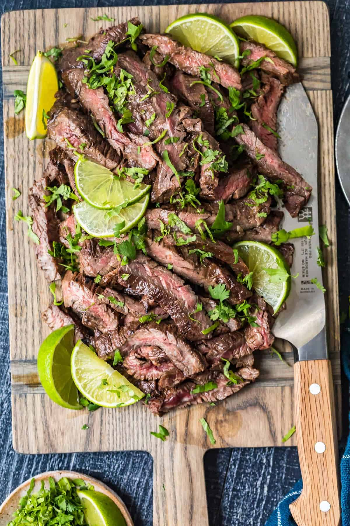 Top down shot of Carne Asada Steak on a board with lime slices