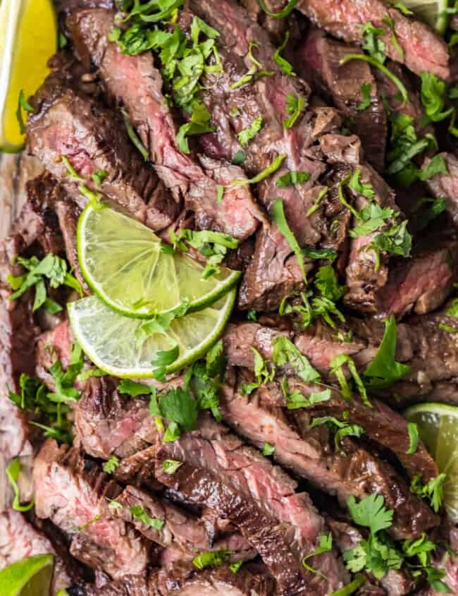 top shot of carne asada steak with sliced lime and cilantro