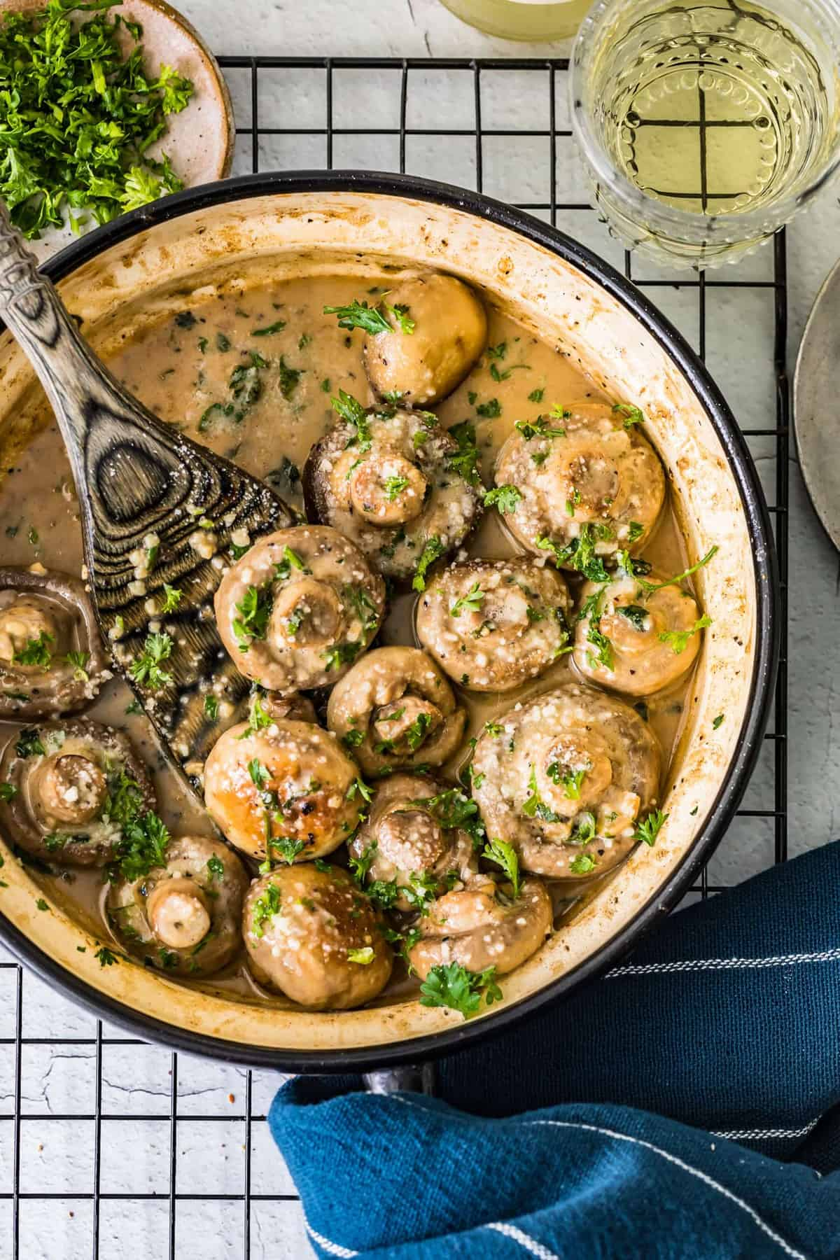 Top shot of creamy garlic mushrooms in a pan with a wooden spoon