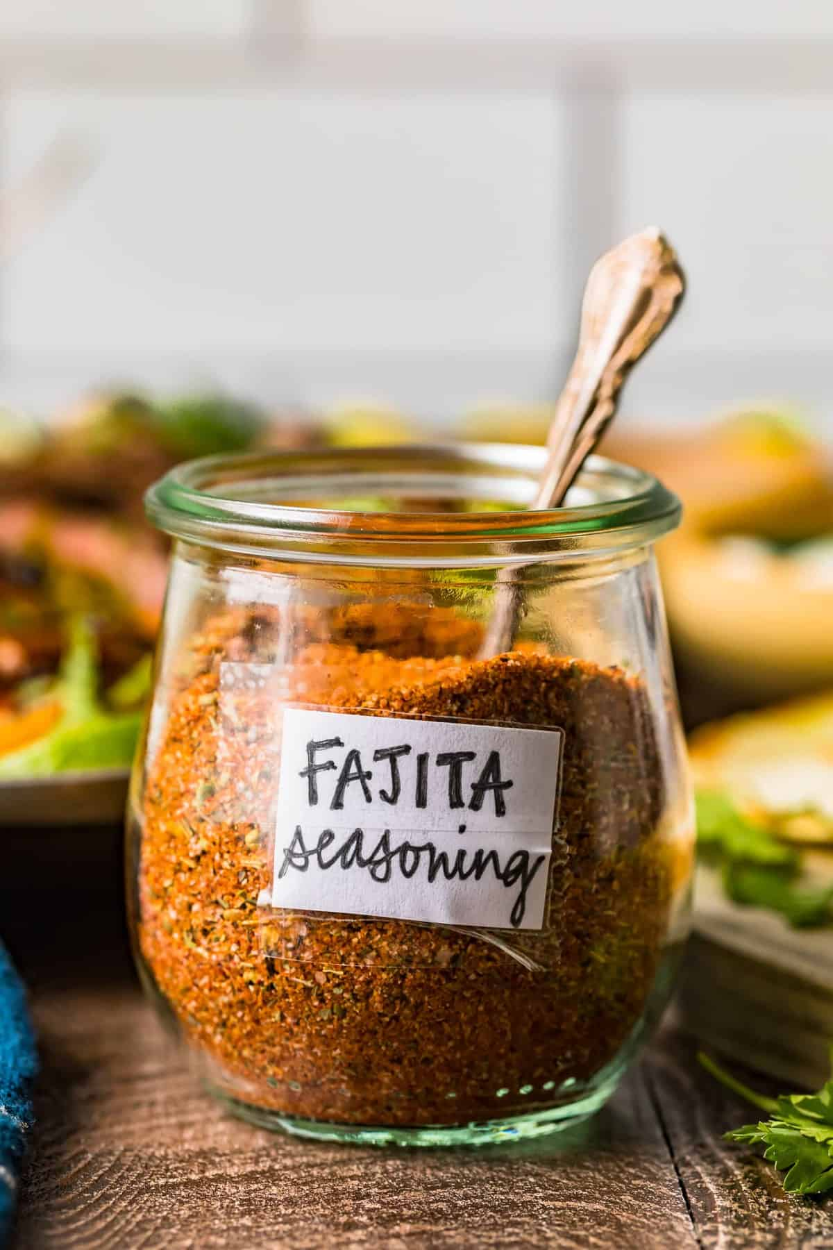 A spoon in a glass jar of fajita seasoning