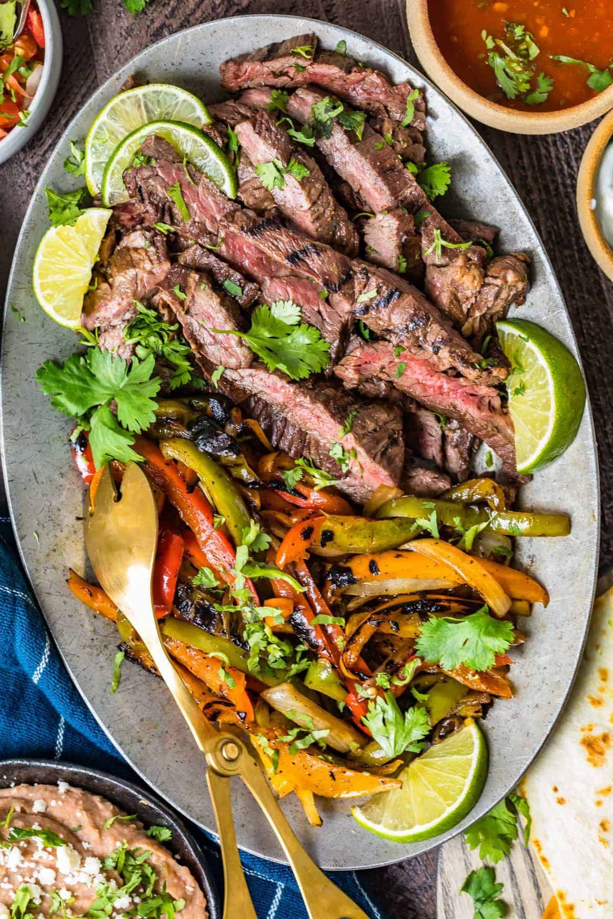 Steak and vegetable fajitas on a large serving plate