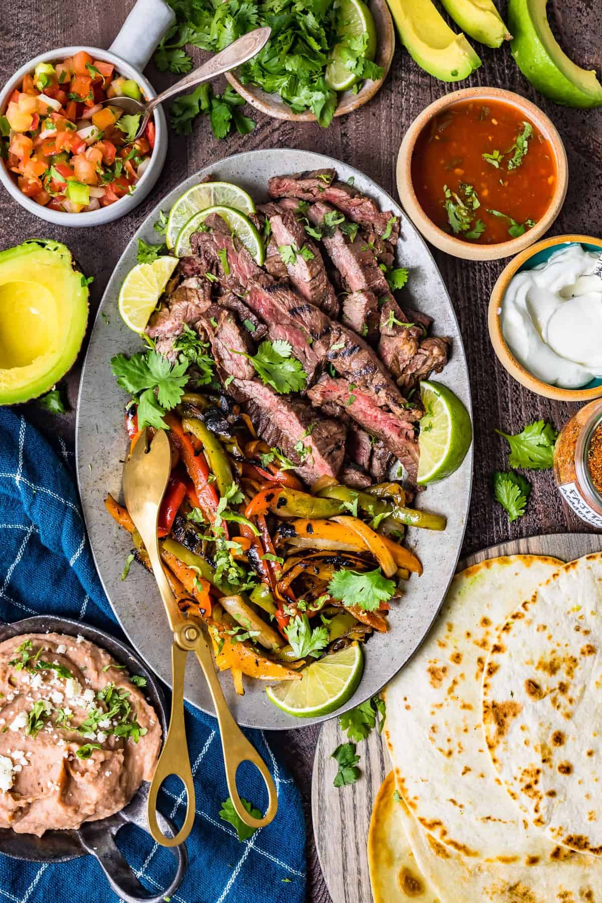 Steak fajitas on a serving plate next to sides and toppings