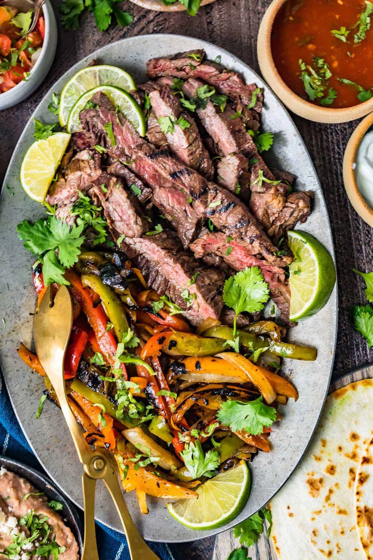 Steak fajitas served with lime wedges