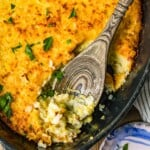 zucchini gratin in pan with wooden spoon