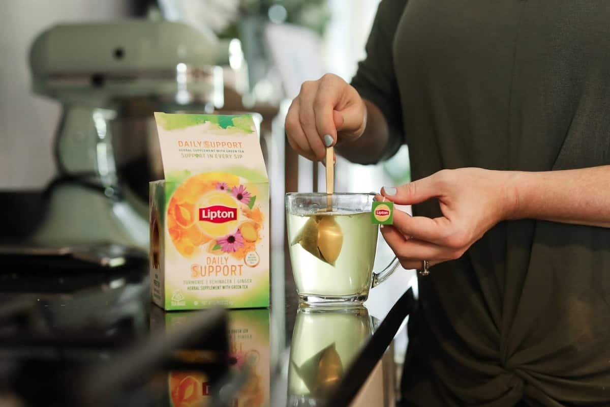 lipton tea box on a counter with a women stirring a tea bag into a mug of water