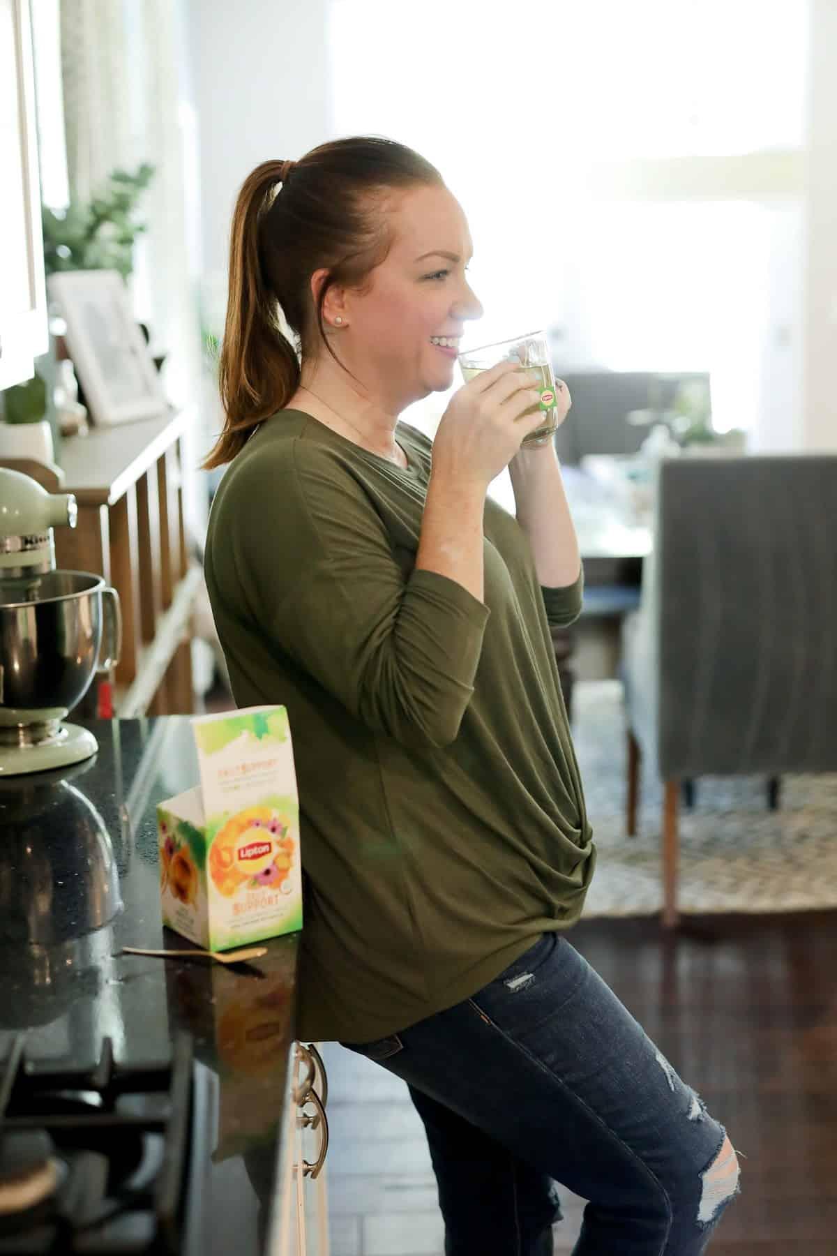 a woman drinking lipton tea in her kitchen
