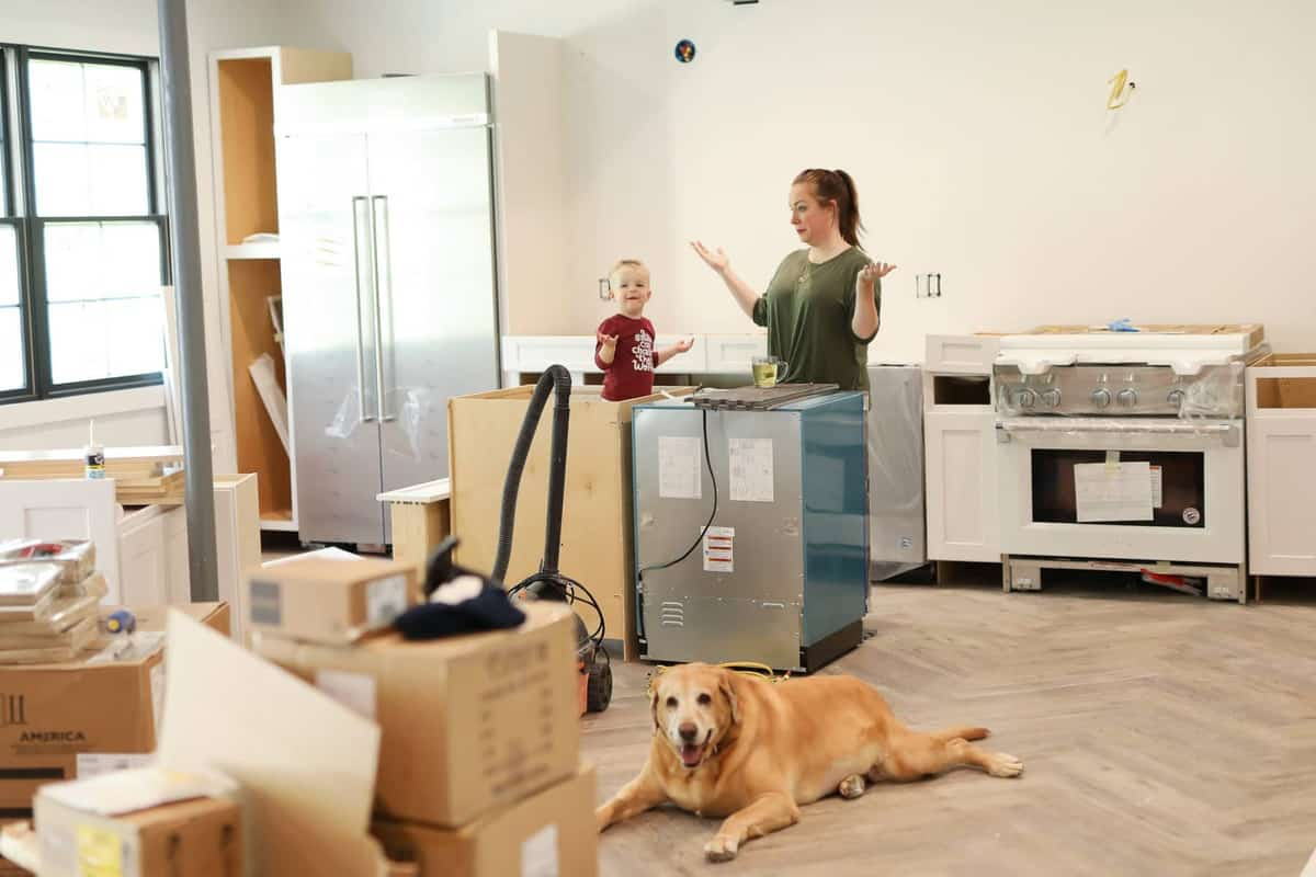 a dog, little boy, and woman inside of a kitchen being remodeled