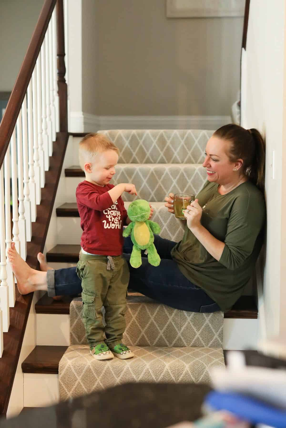 mom and son sitting on stairs with stuffed dinosaur and tea