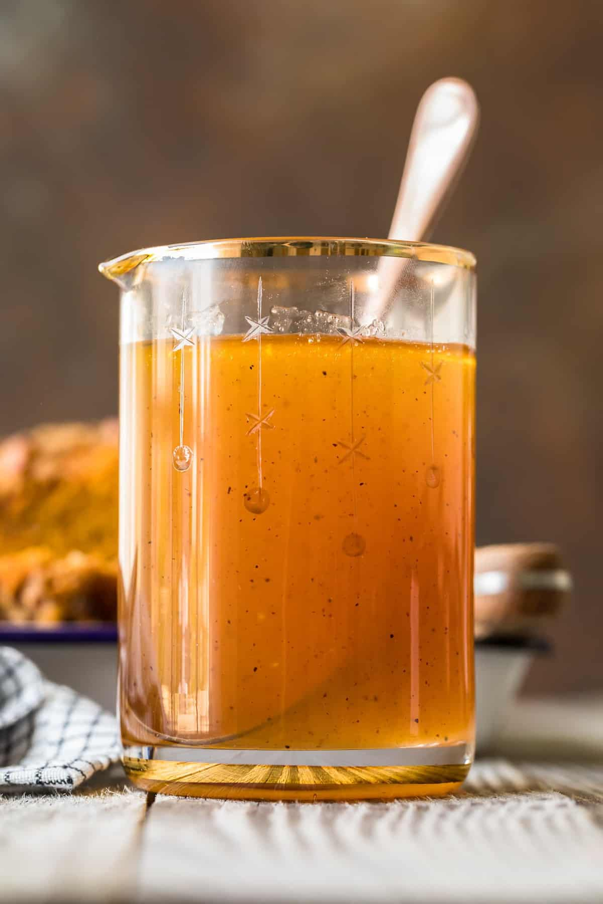 Apple Cider Sauce in a jug with a spoon