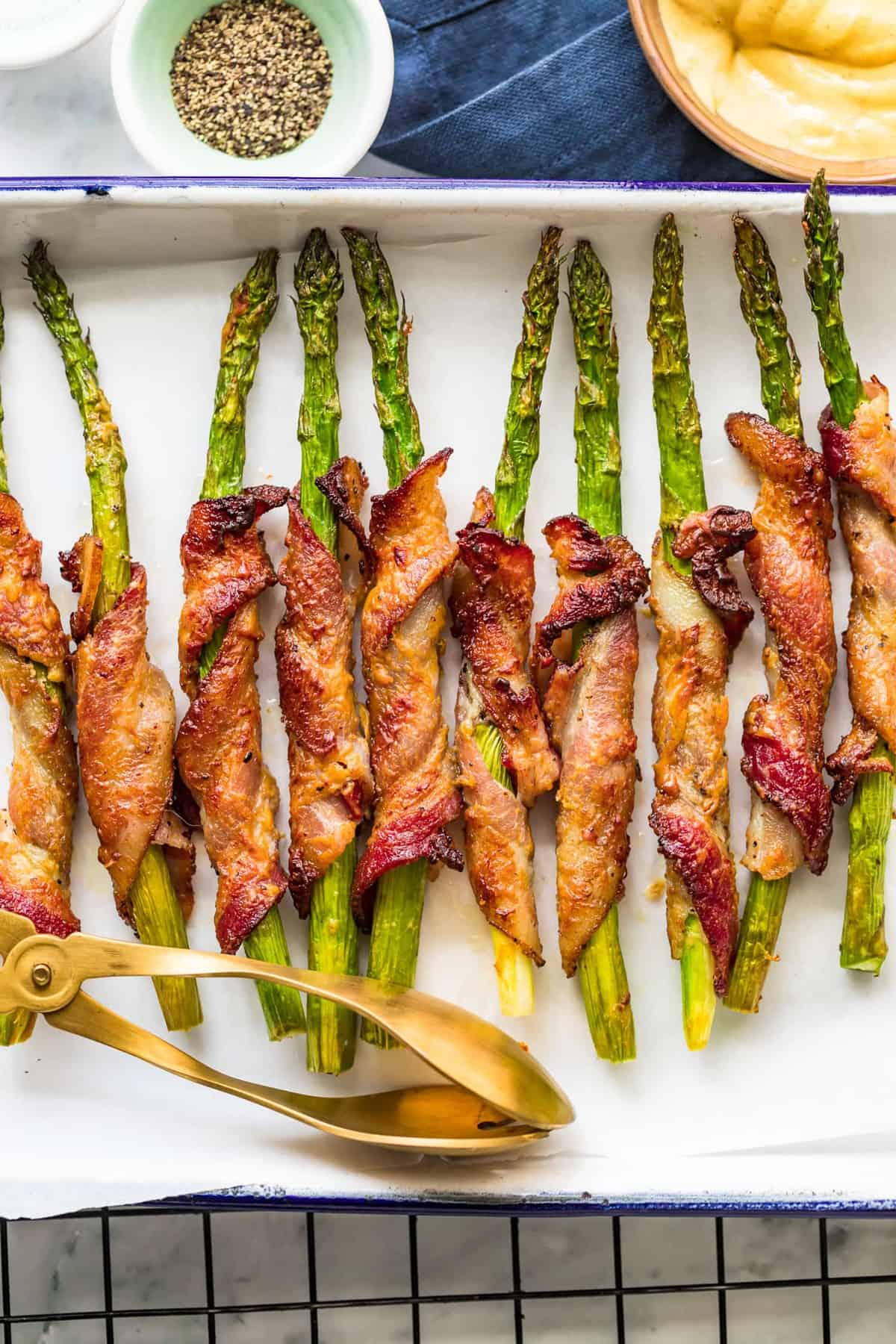 Bacon Wrapped Asparagus baked on a white tray