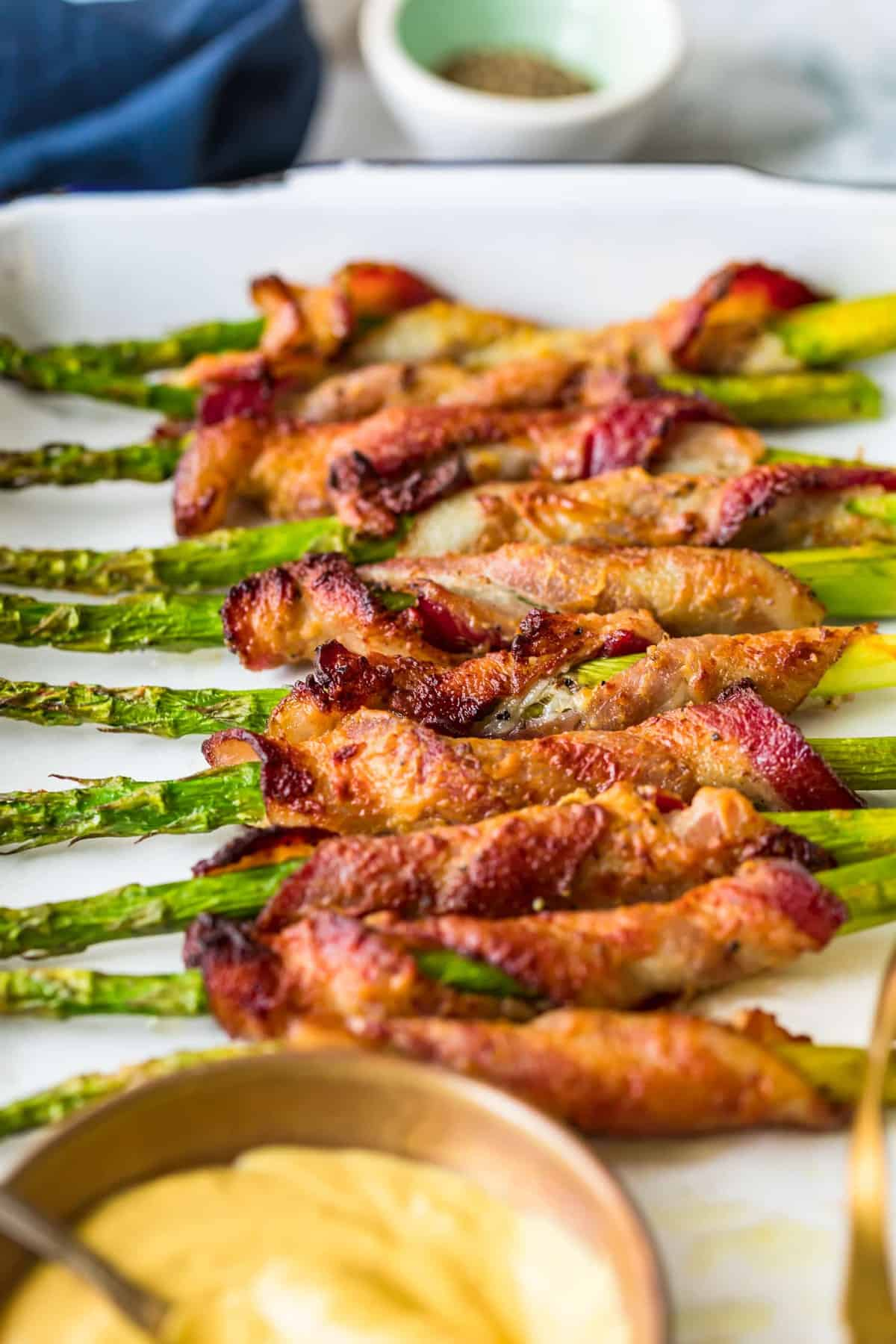 Bacon Wrapped Asparagus in a row on a white plate