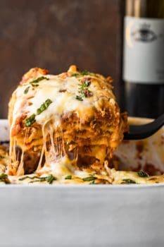 cheesy lasagna coming out of baking dish