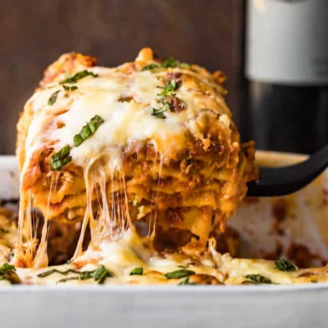 cheesy lasagna coming out of baking dish