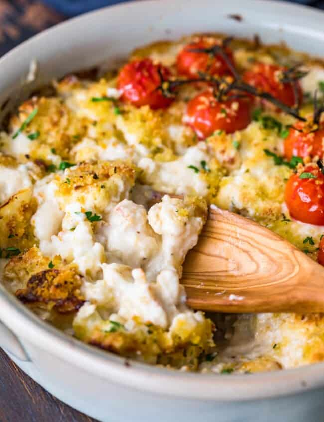 cheesy cauliflower au gratin in dish with wooden spoon
