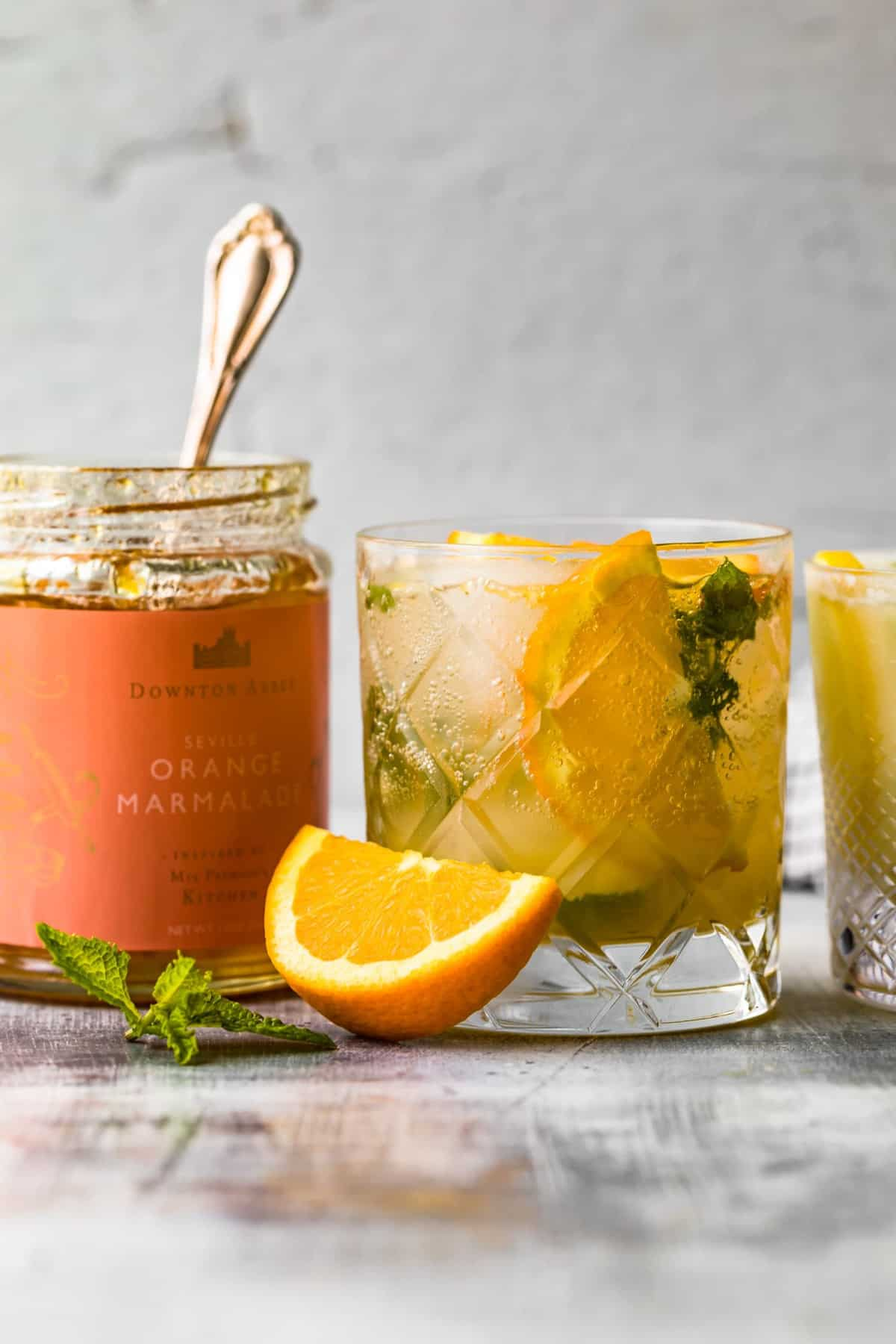 orange marmalade in a jar next to a cocktail on a table with a sliced orange